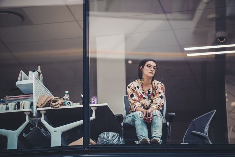 woman in office with no computer on her desk gazing out the window and looking bored