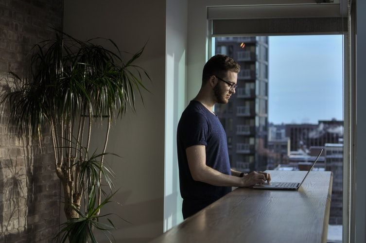 man working alone at home with his laptop on a breakfast bar and view of the city behind him