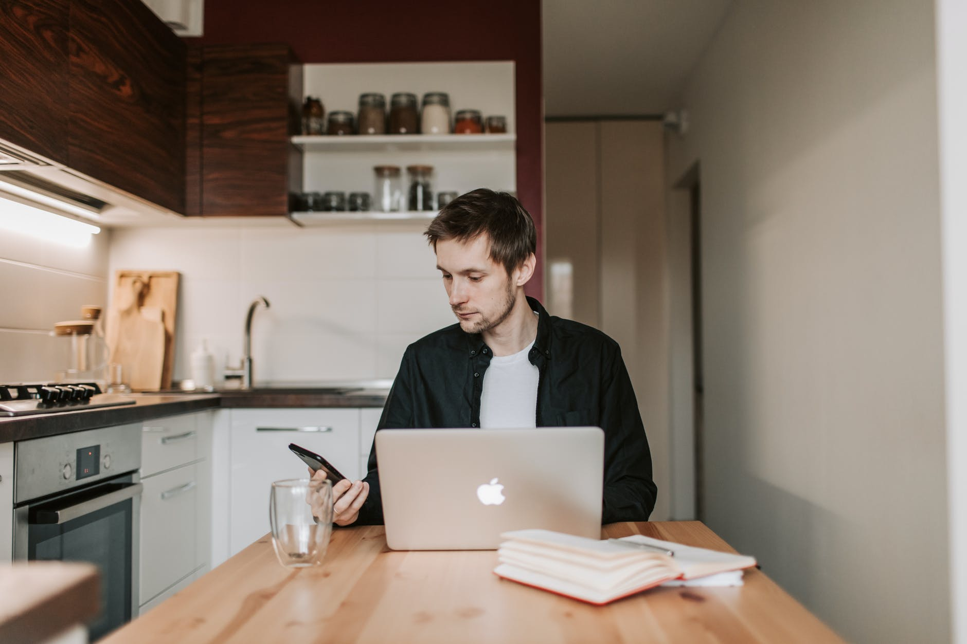 man working on a Macbook in his kitchen while looking expressionless at his phone