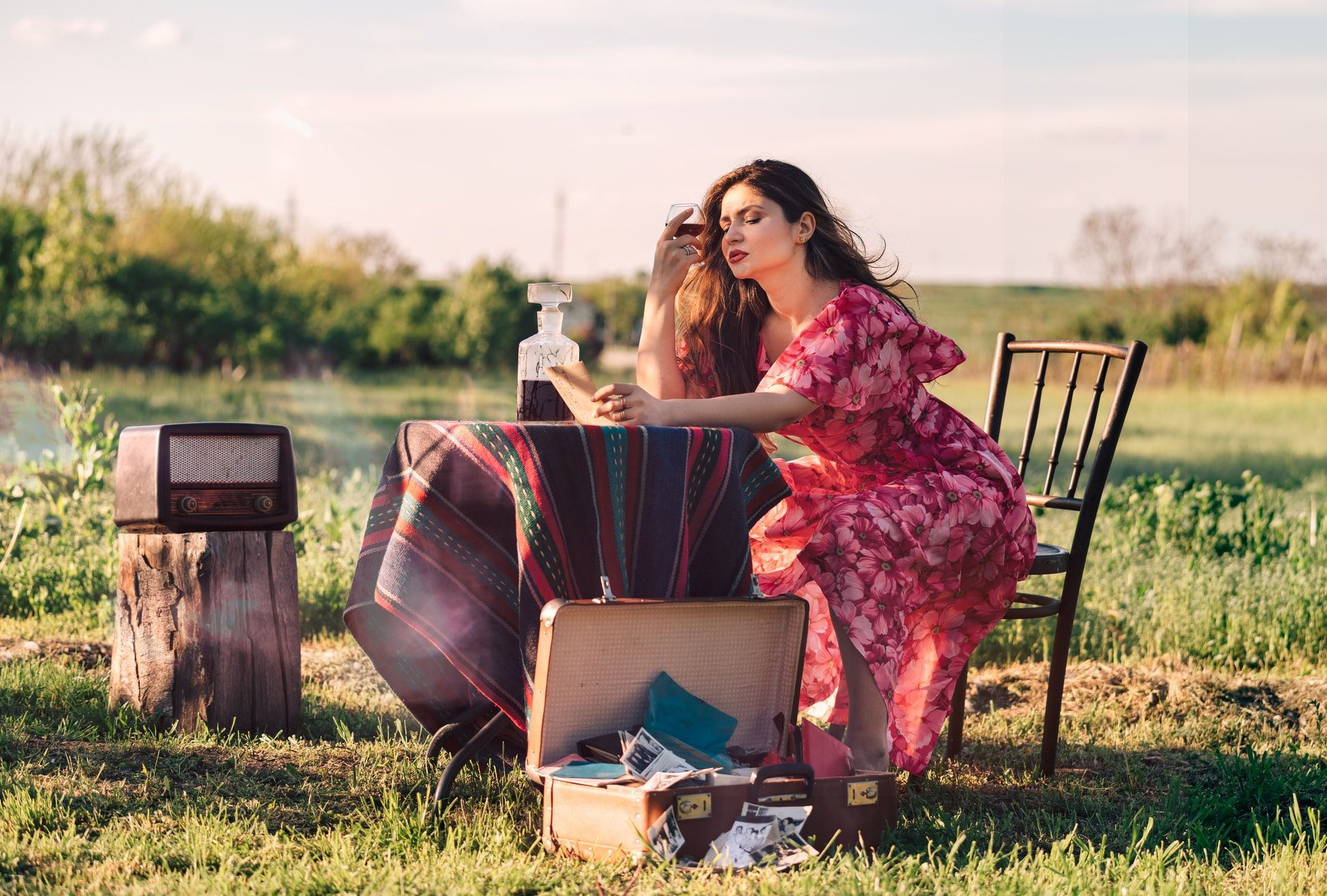 woman sitting at a table in a field drinking brandy and looking bored
