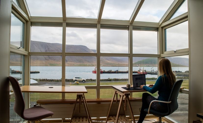 woman working on a laptop with a view from the window of a lake and mountains