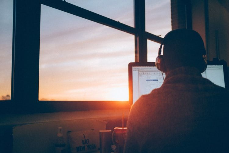 man working on a computer while the sun sets through the window