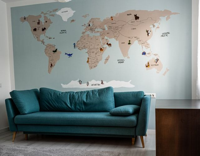 a large world map painted on the wall of a lounge with a sofa in front of it