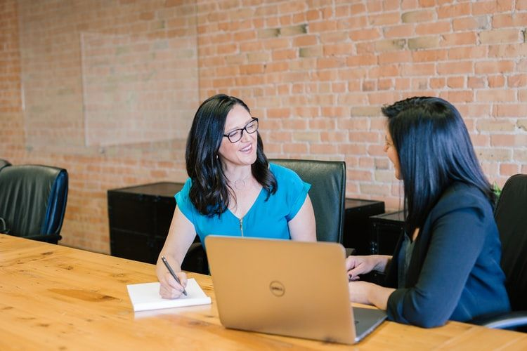 woman with a laptop in a meeting room talking to another woman who is taking notes