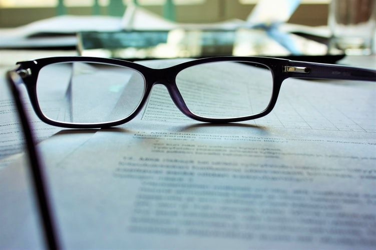 a pair of reading glasses placed on top of a contract with lots of wording
