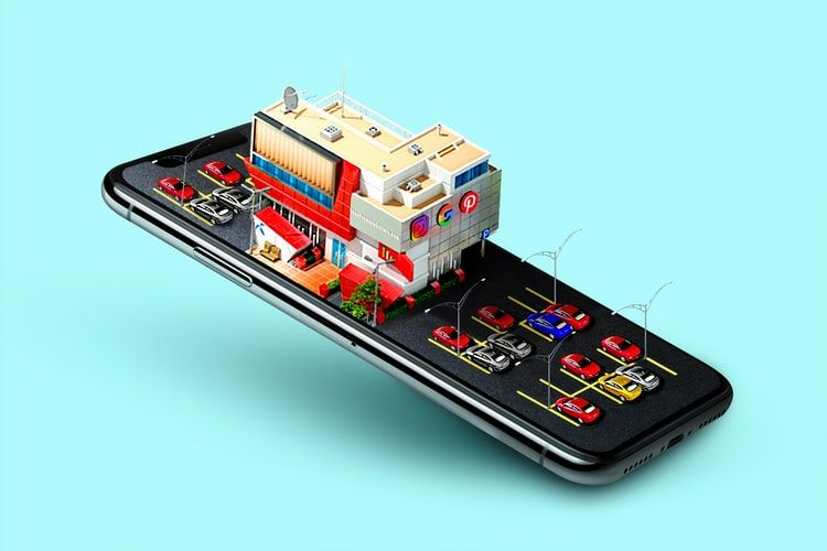 a smartphone with a 3D model of a building and car park on its screen indicating online reviews