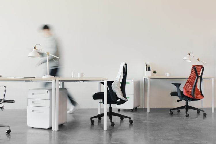 desks in a office with no computers on them and a blurred person rushing past in the background