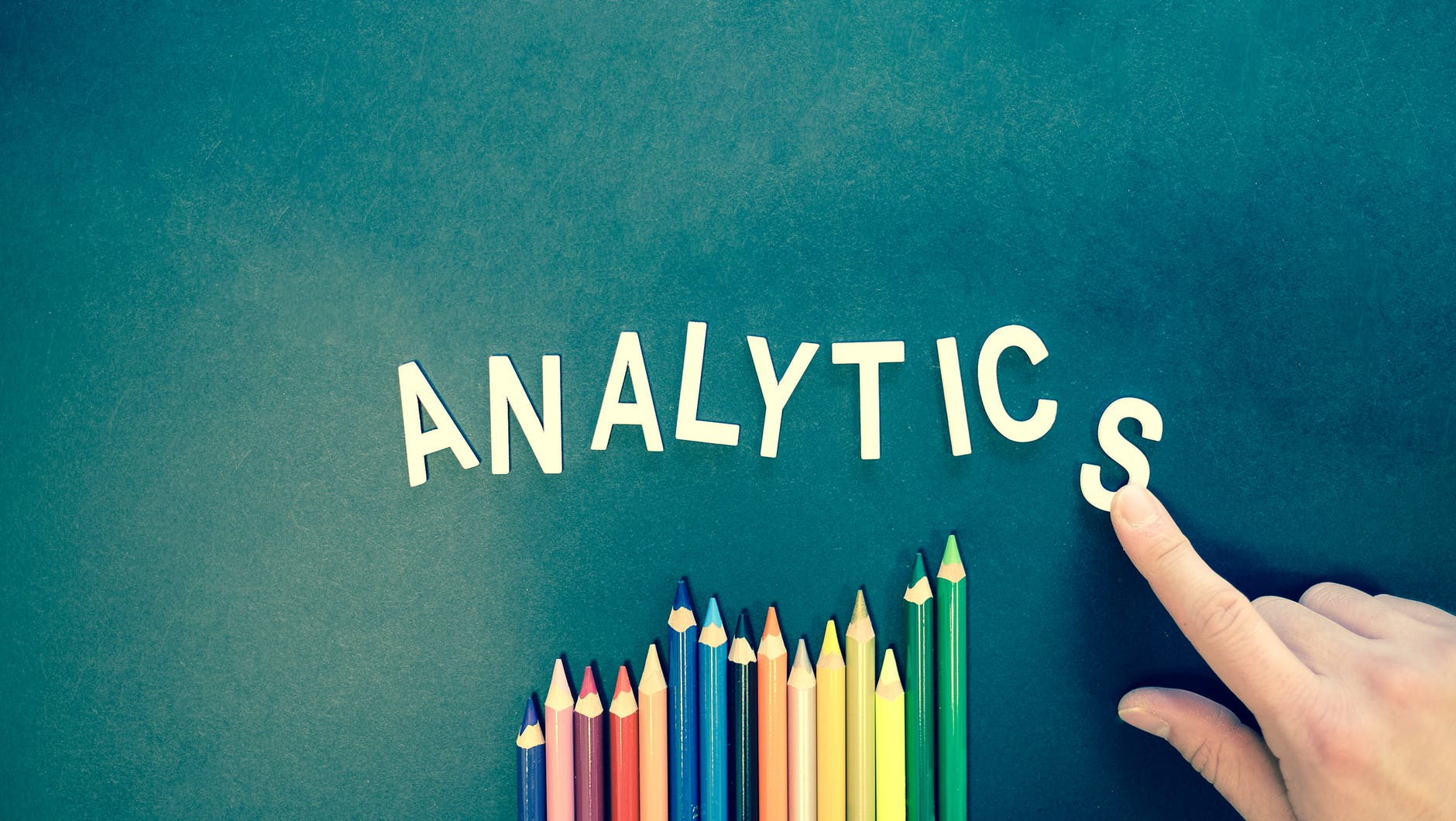 the word analytics on a background with an assortment of coloured pencils below it