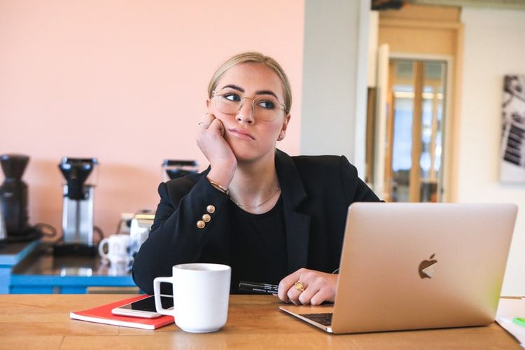 woman working from home and gazing into the distance with her chin in her hand