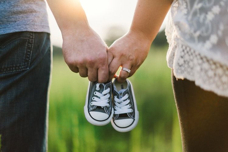 man and woman holding hands and holding a pair of small baby shoes