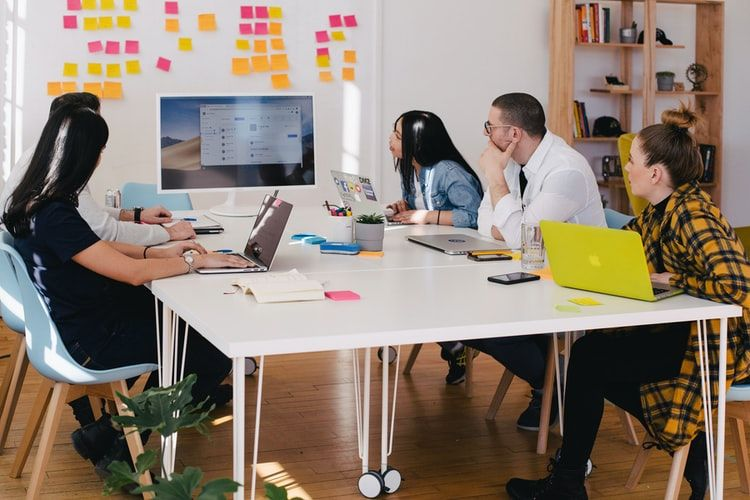 group of people in a team meeting in an office with a large screen and post it notes