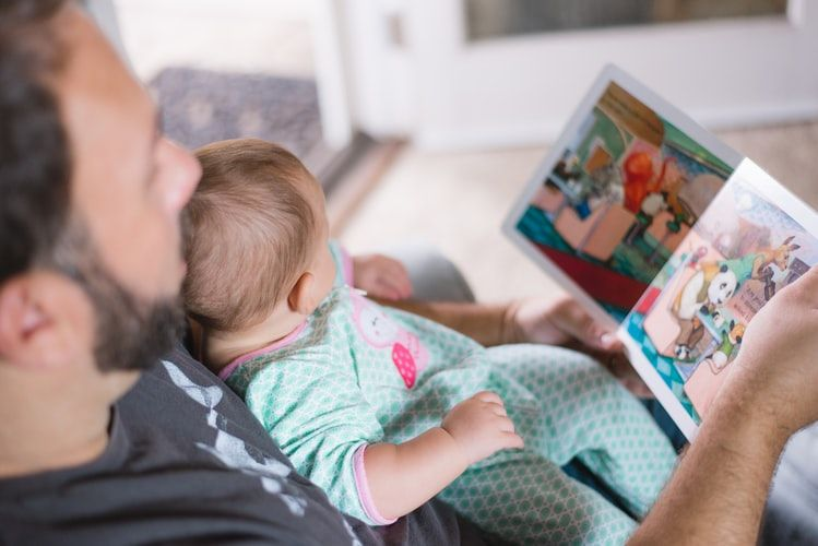 a dad with a baby sitting in his lap looking at a picture book together