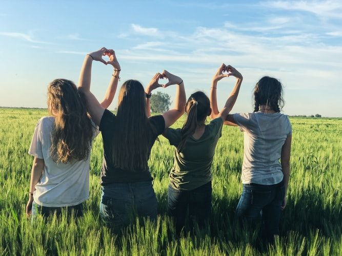 four women in a field holding up hand heart signs