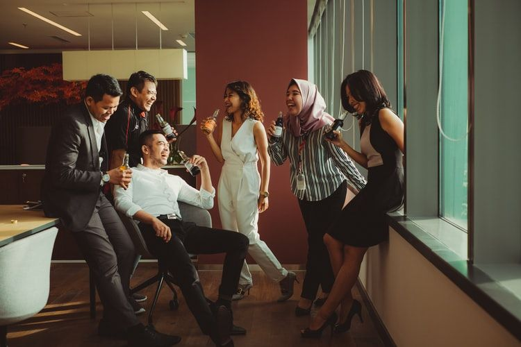 group of coworkers in an office drinking from soda or beer bottles and laughing