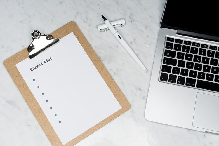 a guest list on a clipboard lying on a desk next to a laptop