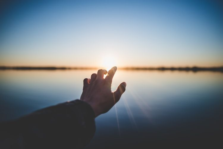 hand reaching out across a body of water towards a setting sun and the distant bank
