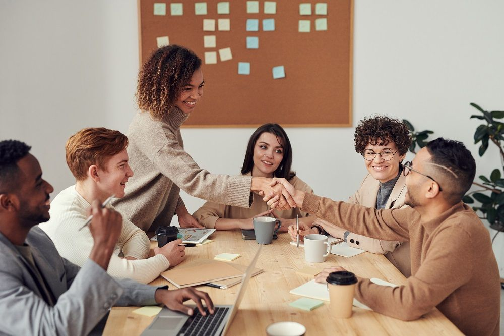 group of smiling coworkers in meeting with two of them shaking hands