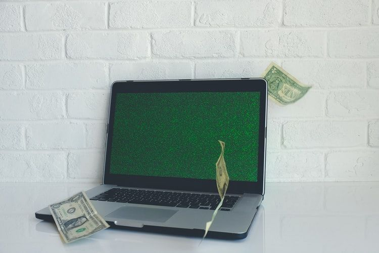 laptop on a desk with some dollar bills floating around it