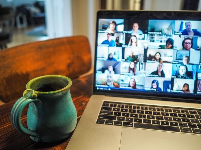 open laptop on a table with a mug of coffee showing multiple people on a video call