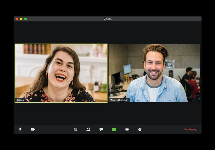 two people on a video call smiling, one at home and one in an office