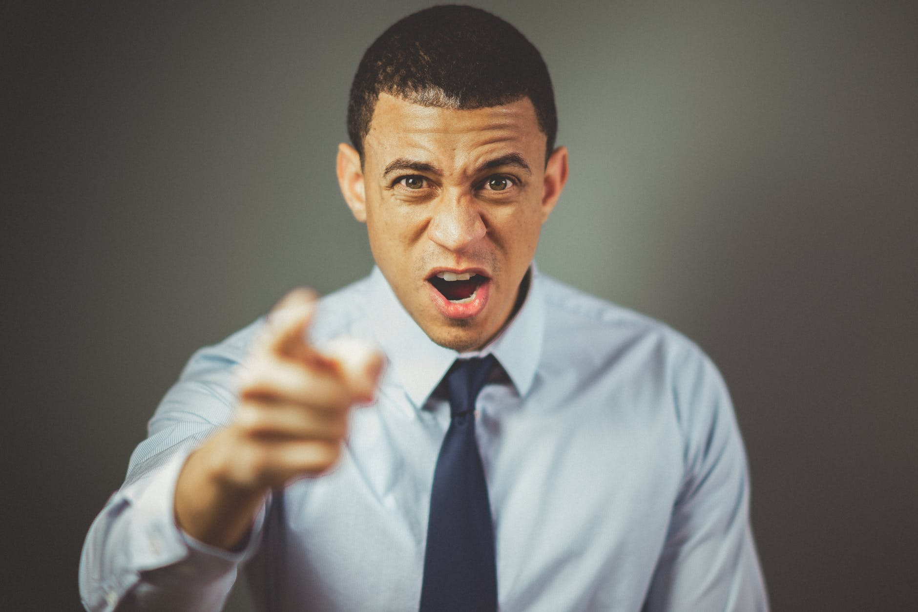 man in shirt and tie shouting and pointing at the camera