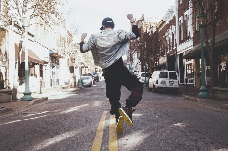 man walking down the street and jumping for joy