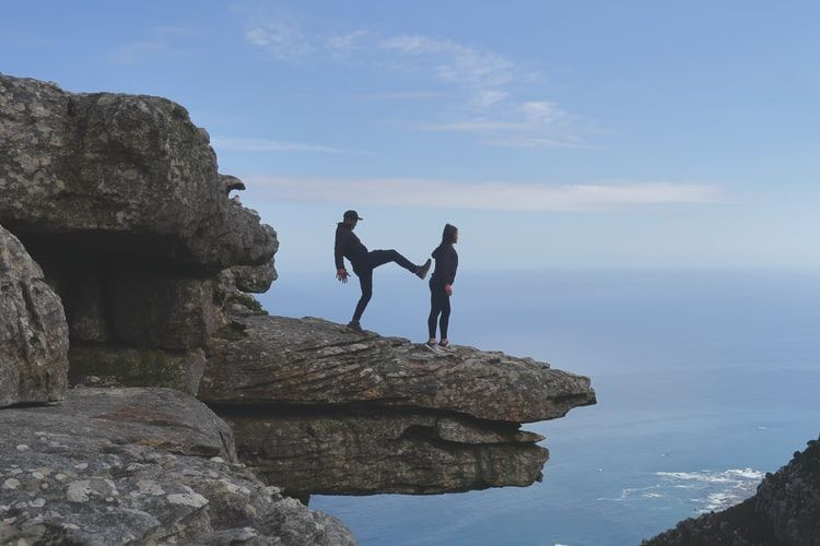 man pretending to kick a woman off the edge of a cliff