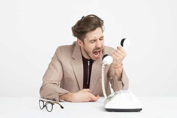 angry man in a suit jacket screaming into a telephone receiver