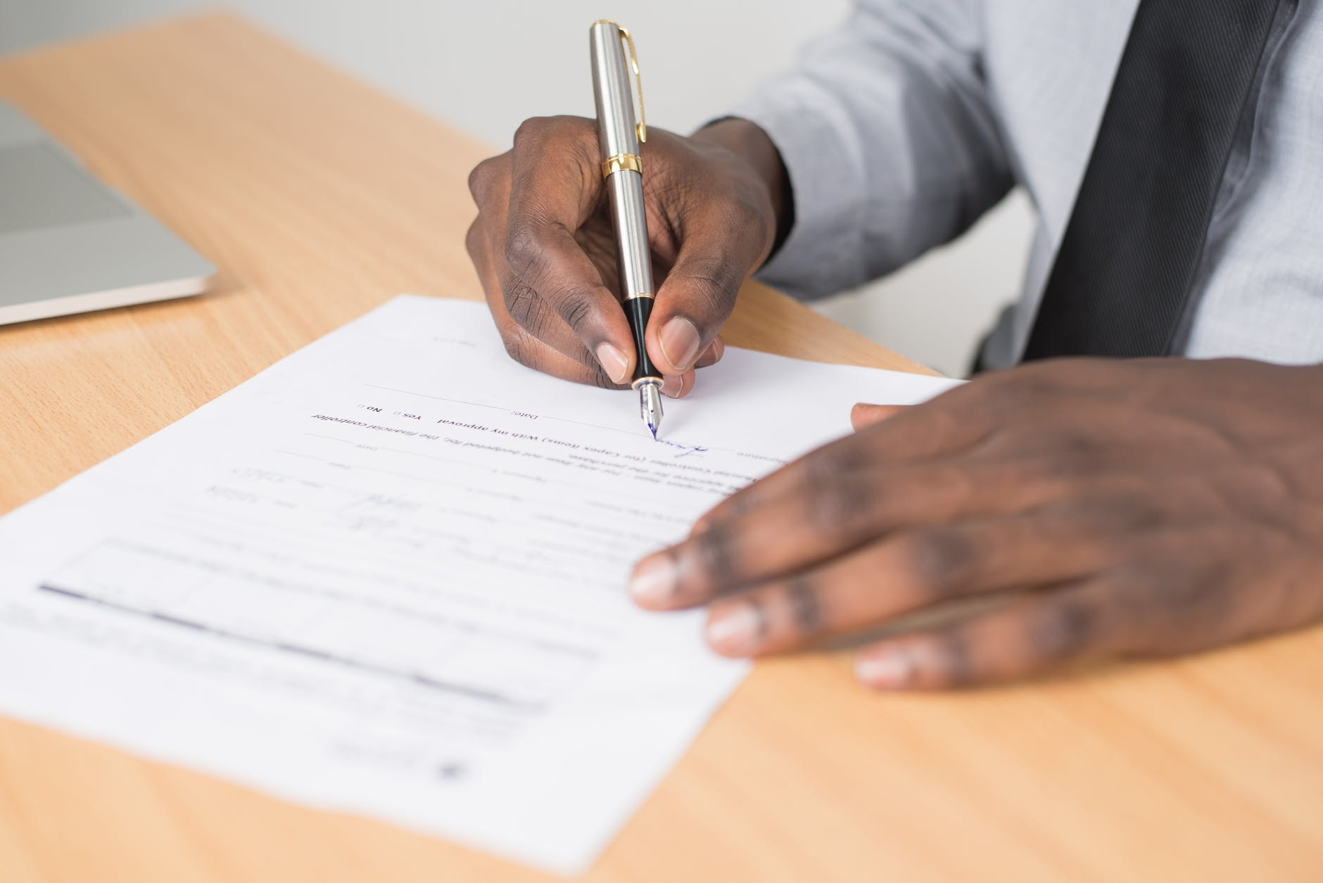 man sitting at a desk signing a form