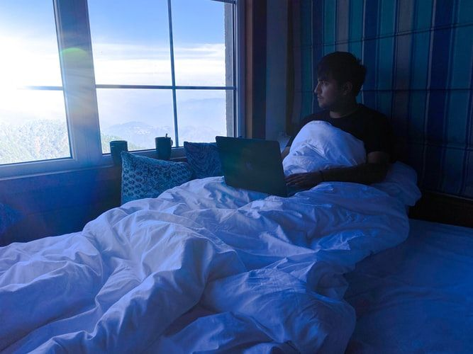 man using a laptop in bed in an early morning light