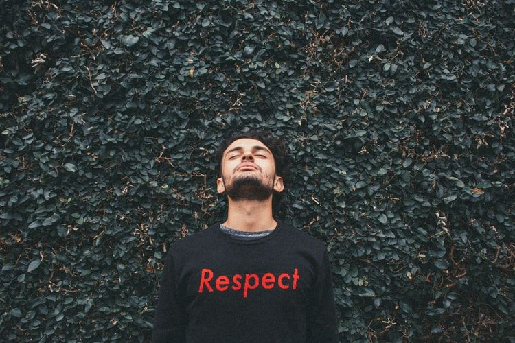 man wearing a sweatshirt with the word respect on the front