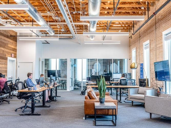 trendy open plan office with high ceiling and modern furniture