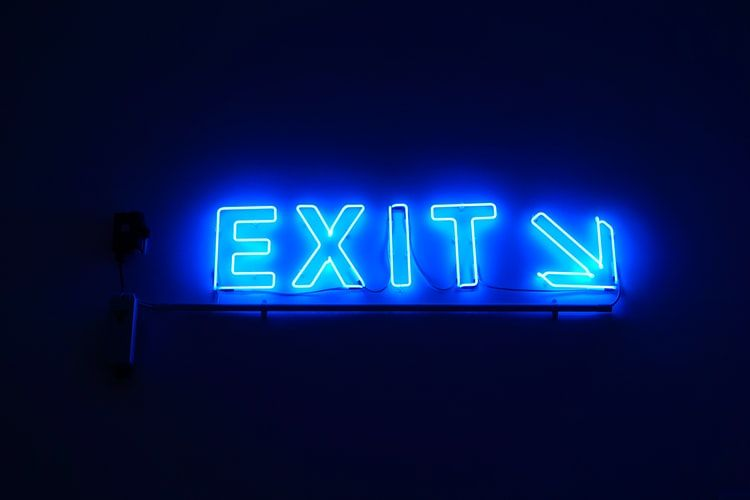 blue neon sign saying Exit with an arrow pointing down
