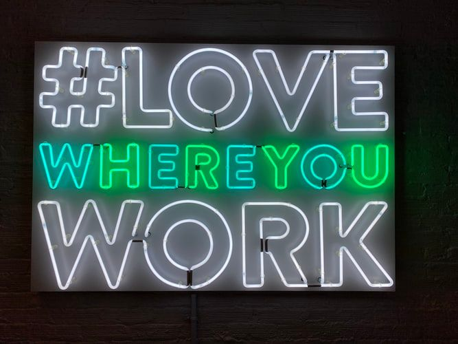 neon sign saying 'Love Where You Work'