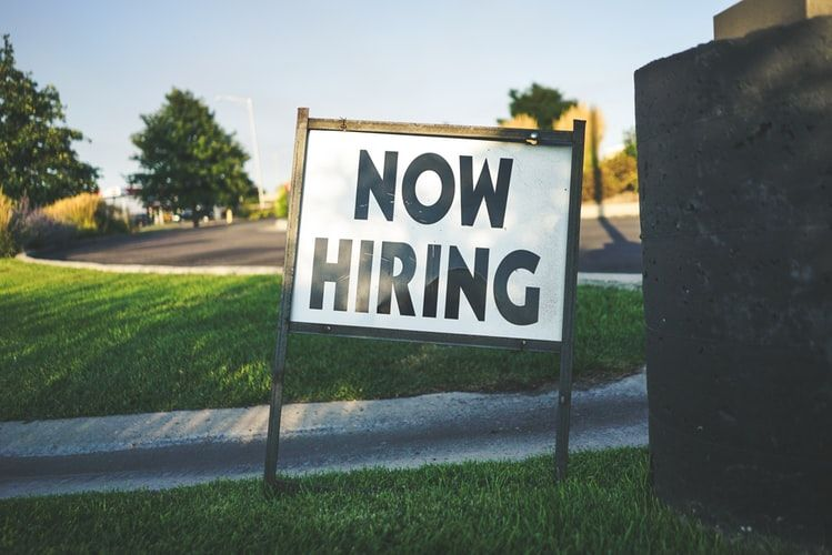 sign in grass saying Now Hiring