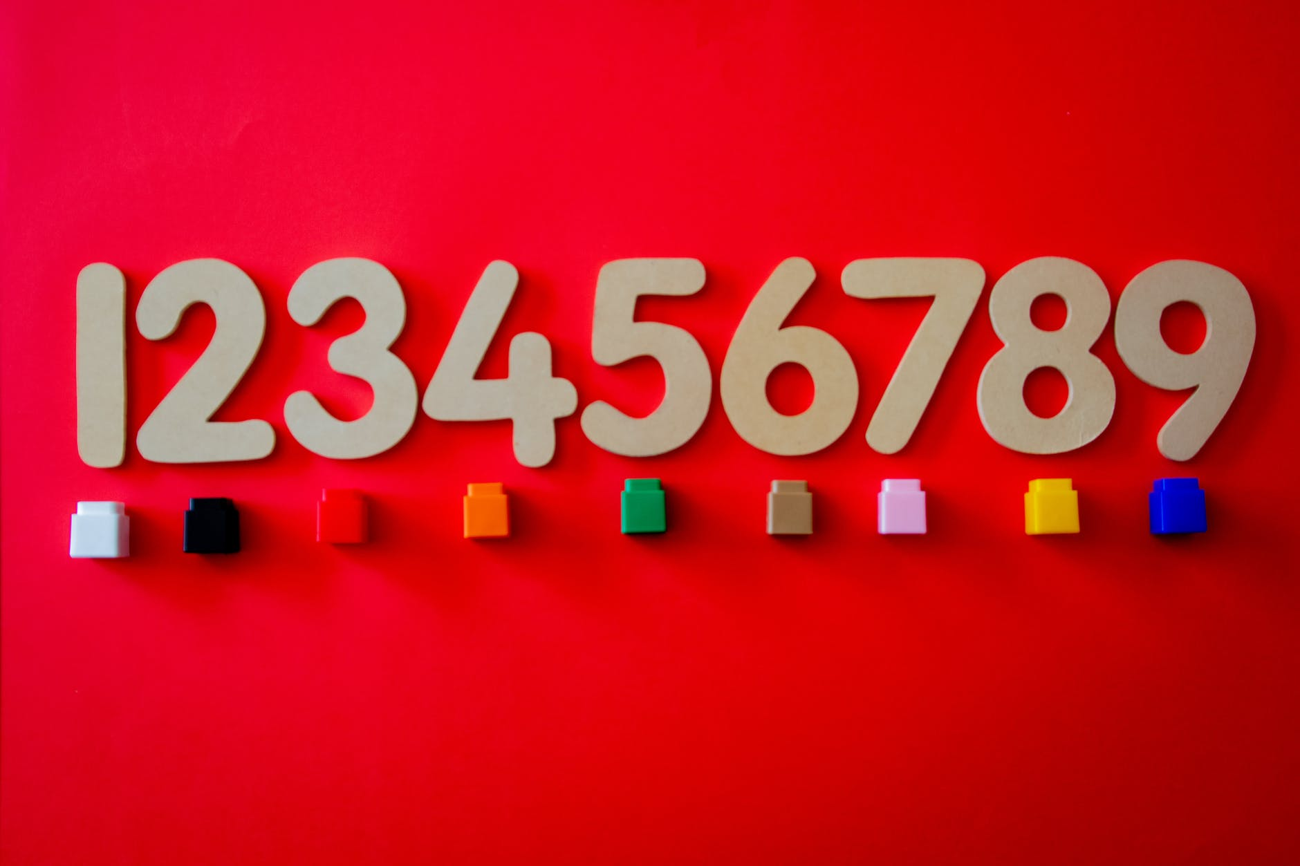 cut out numbers on a red background with different colored blocks underneath each