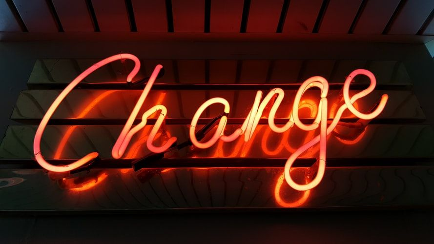 orange neon sign saying Change
