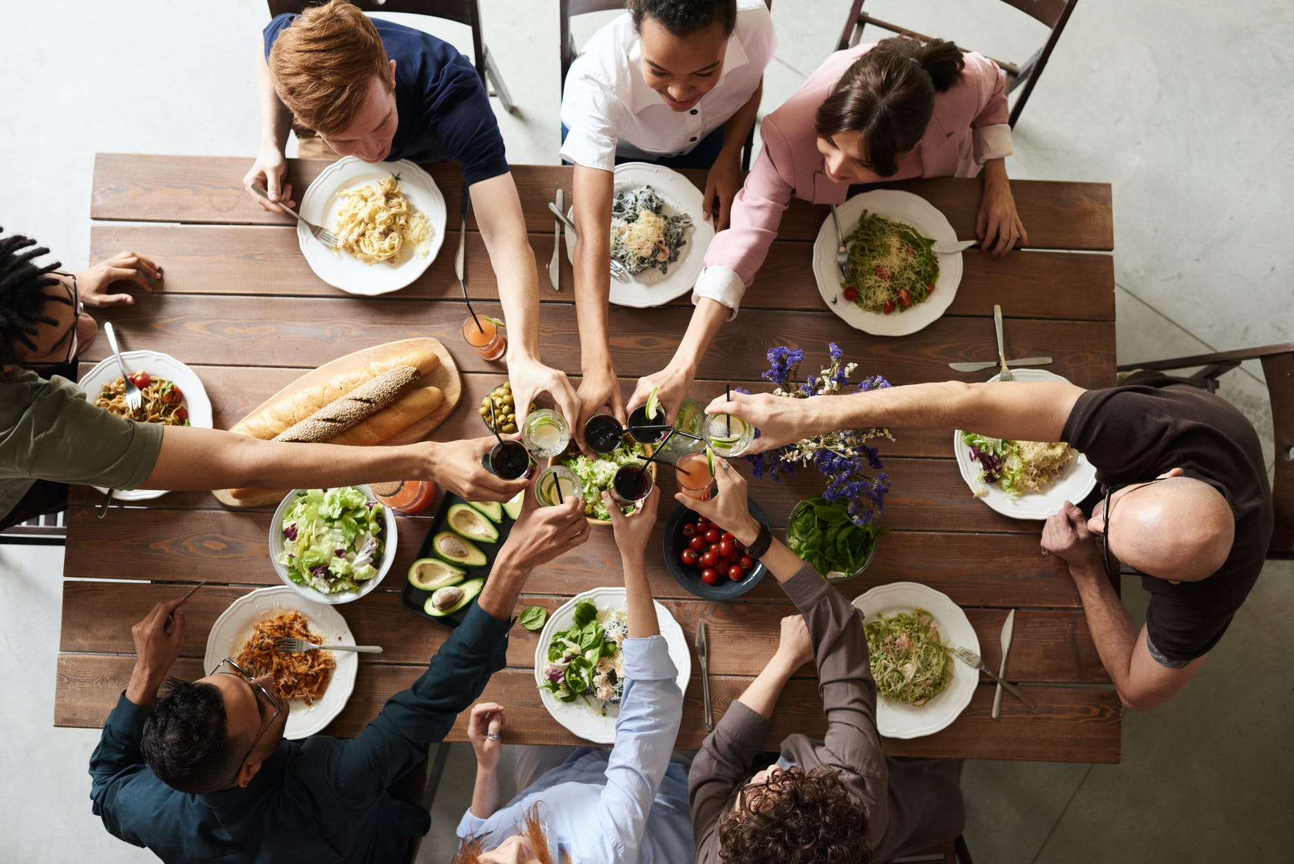 aerial shot of 8 people sitting around a table eating lunch and clinking their glasses together