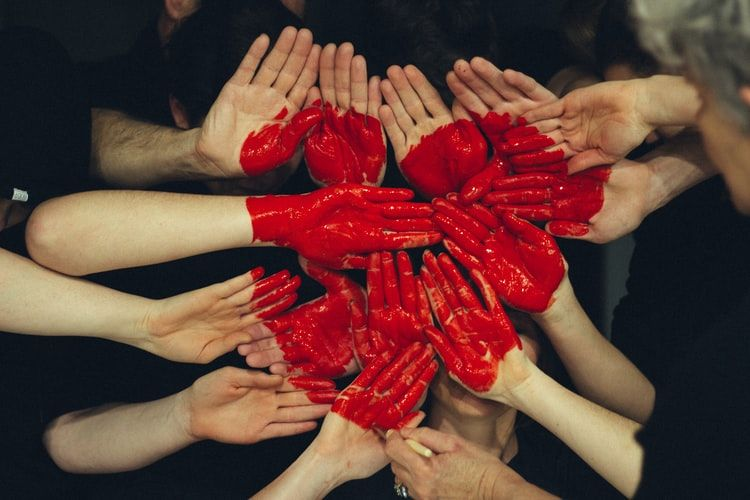 group of people with their hands painted red to make a heart shape