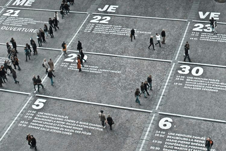 people standing on a large scale calendar which has been blocked out and painted on the ground