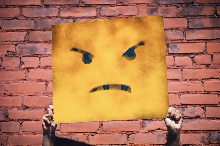 person holding up a yellow square with an angry face drawn on it