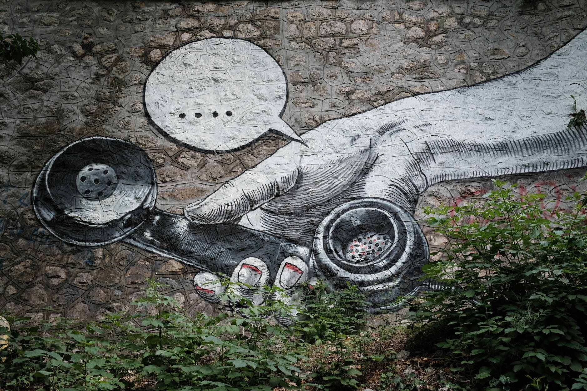 wall art graffiti of a hand holding out an old fashioned telephone receiver