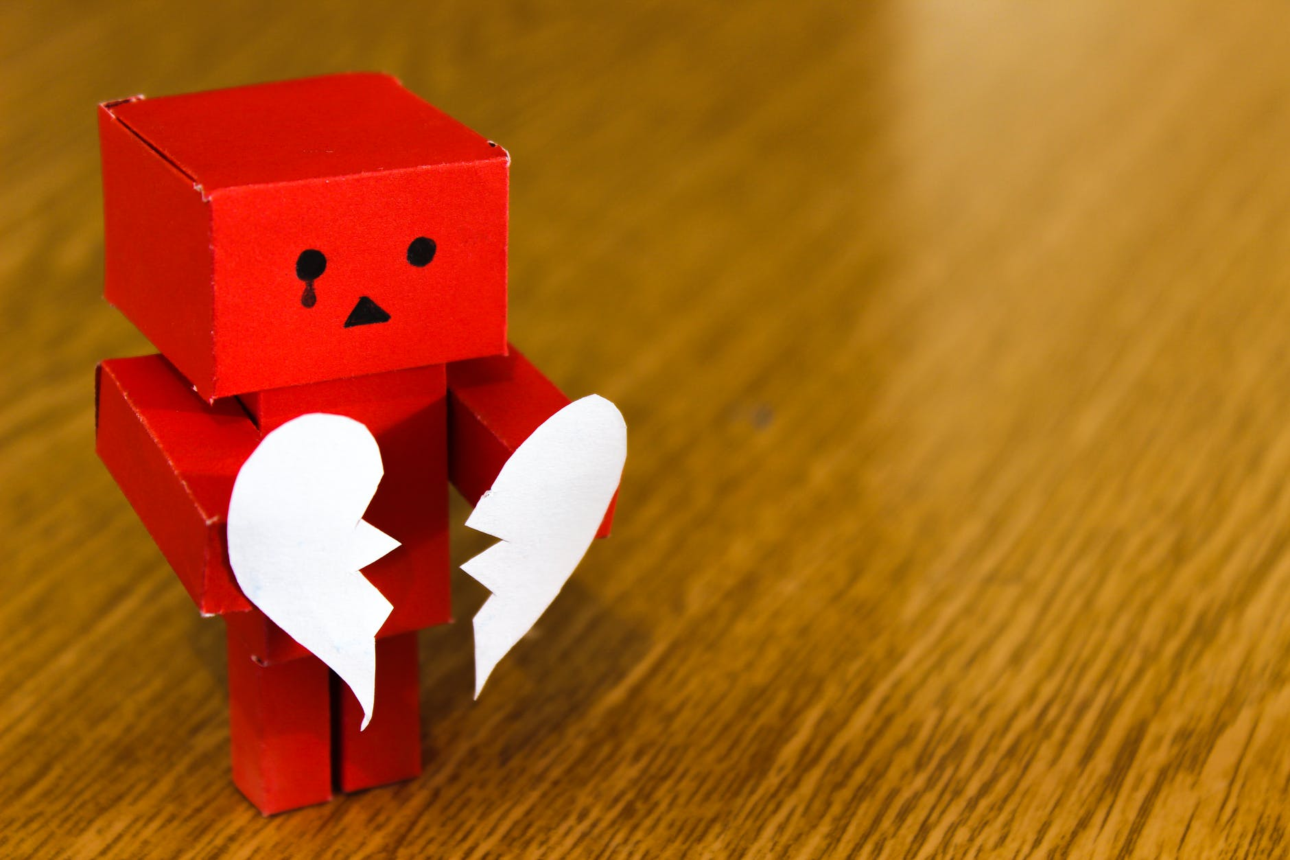 red cardboard robot with a tear in his eye holding a paper broken heart