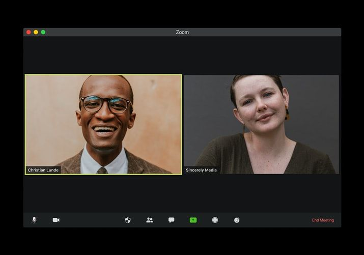 a laptop screen showing a video call with two people