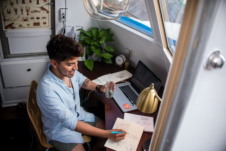 smiling man looking productive with a laptop and notebooks while working from home