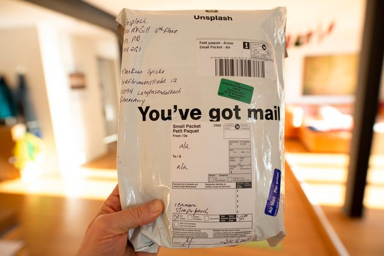 hand holding a postal package saying 'you've got mail'