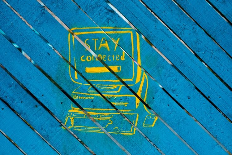 yellow street art painting of a computer with the words Stay Connected on the screen