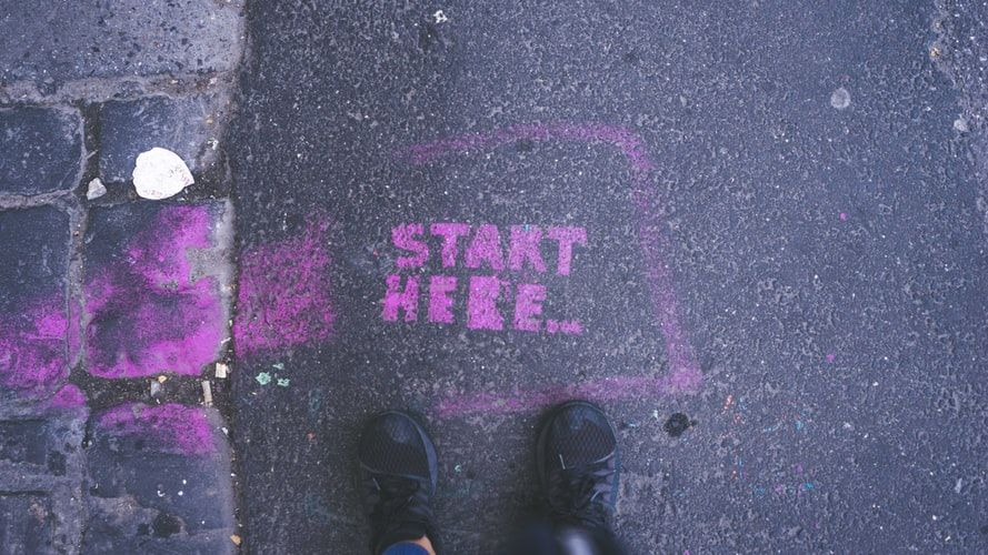 feet standing in front of the words Start Here stenciled on the ground in purple paint