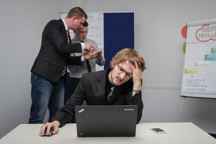 man at desk looking at laptop and grimacing
