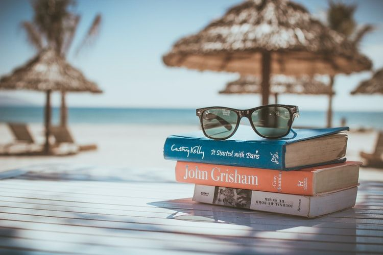pile of books and sunglasses on a table on a beach